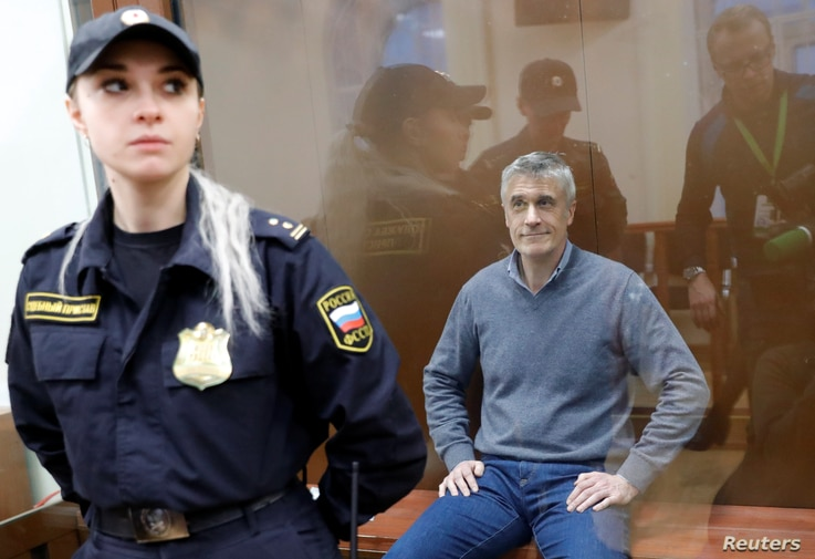 Founder of the Baring Vostok private equity group Michael Calvey, who was detained on suspicion of fraud, sits inside a defendants' cage as he attends a court hearing in Moscow, Feb. 15, 2019.