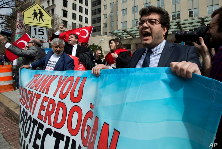 Supporters of Turkish President Recep Tayyip Erdogan hold banners during a rally outside the Brookings Institution in Washington, where Erdogan spoke, March 31, 2016.