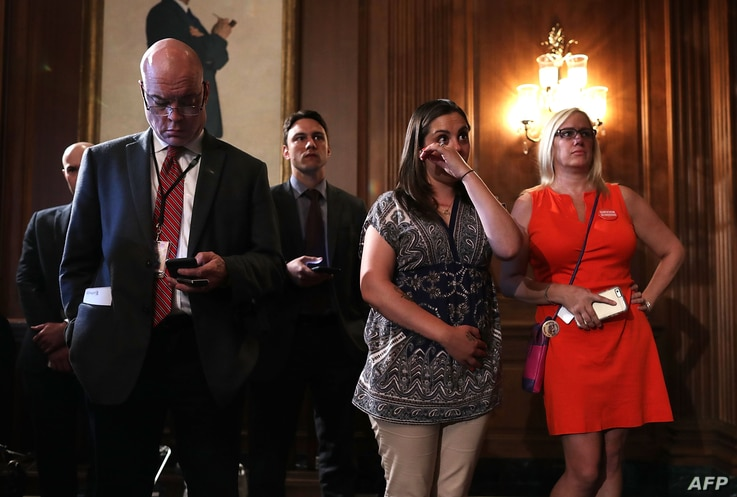 Erica Smegielski (2nd R), daughter of slain principal Dawn Hochsprung of Sandy Hook Elementary School, wipes away tears as she listens to a news conference on gun control at the Capitol in Washington, D.C., June 20, 2016.