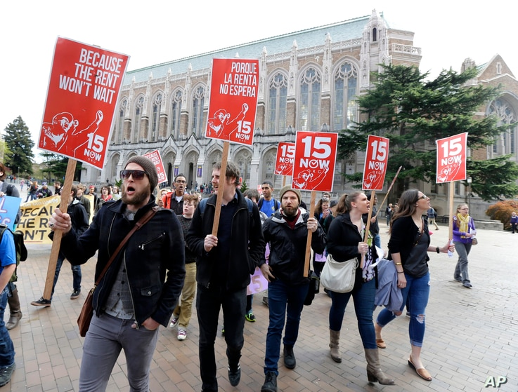 FILE - Protesters in Seattle, Washington, rally in support of raising the minimum wage to $15 an hour, April 1, 2015.