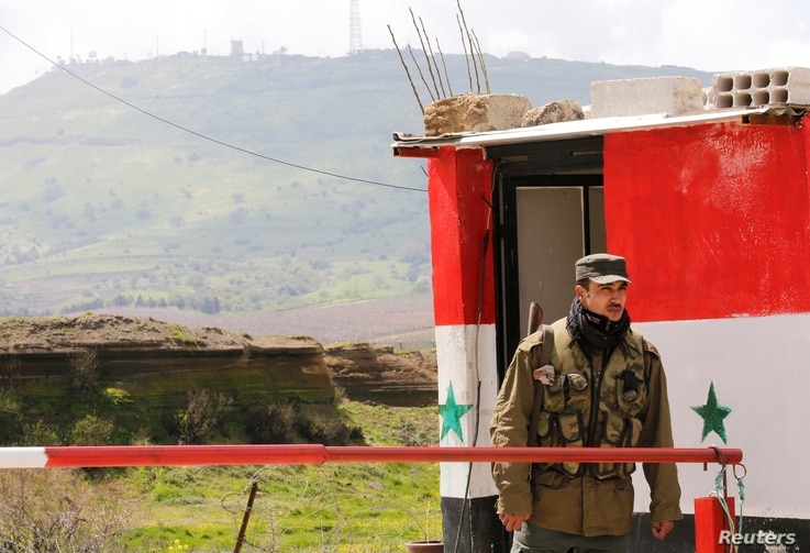 A Syrian army soldier stands at a checkpoint at the Quneitra crossing between the Israeli-controlled Golan Heights and Syria, seen from the Syrian side in Quneitra, Syria, March 26, 2019.