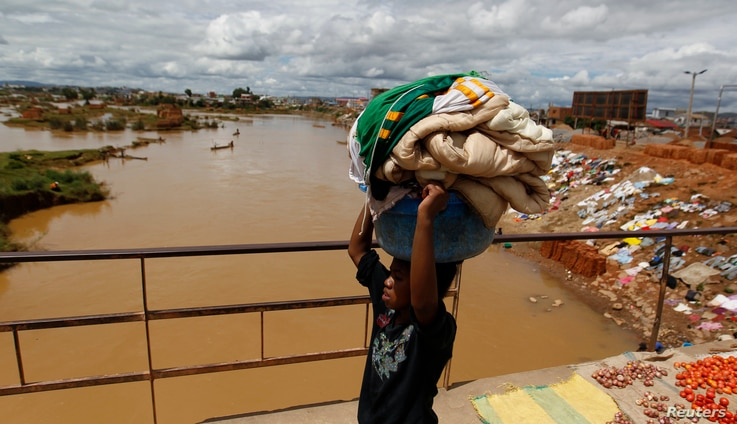 FILE - A girl carries laundry to be washed as she walks along a bridge near the banks of Ikopa river in Madagascar's capital Antananarivo.