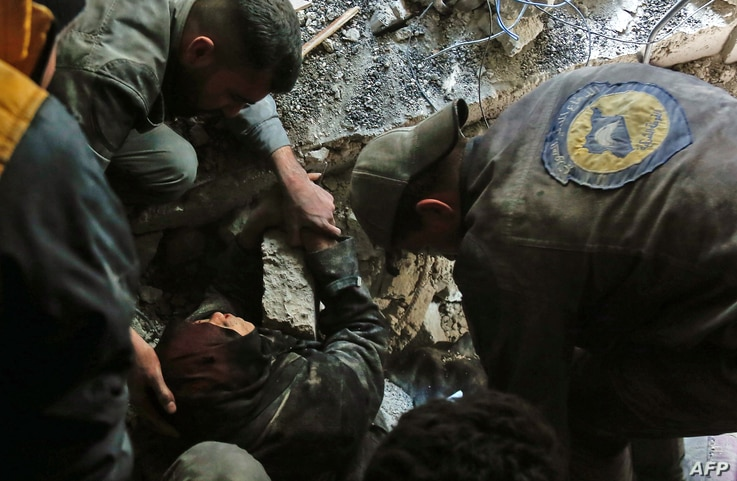 FILE - Volunteers of the Syrian Civil Defense, known as the White Helmets, rescue a woman from the rubble of a building after an airstrike in Douma, eastern Ghouta, March 19, 2018.