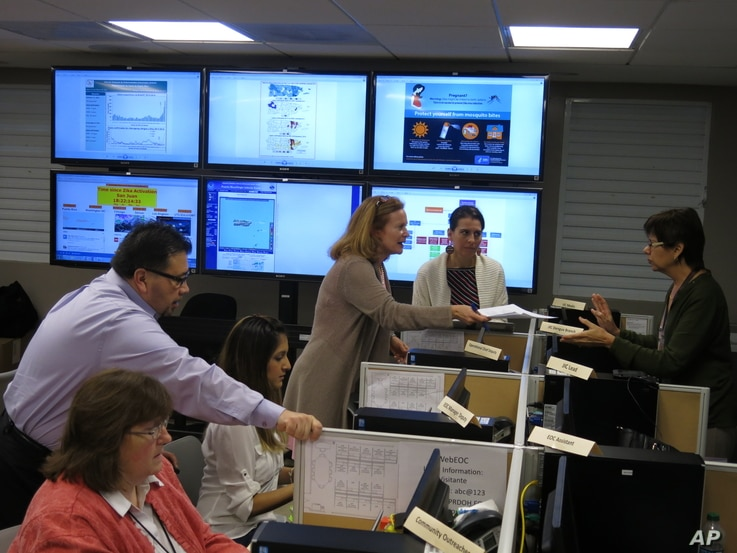 FILE - Workers from the Puerto Rico Health Department and U.S. Centers for Disease Control and Prevention review Zika-related data collected by the island's health dept and CDC workers in San Juan, Puerto Rico, Feb. 24, 2016.