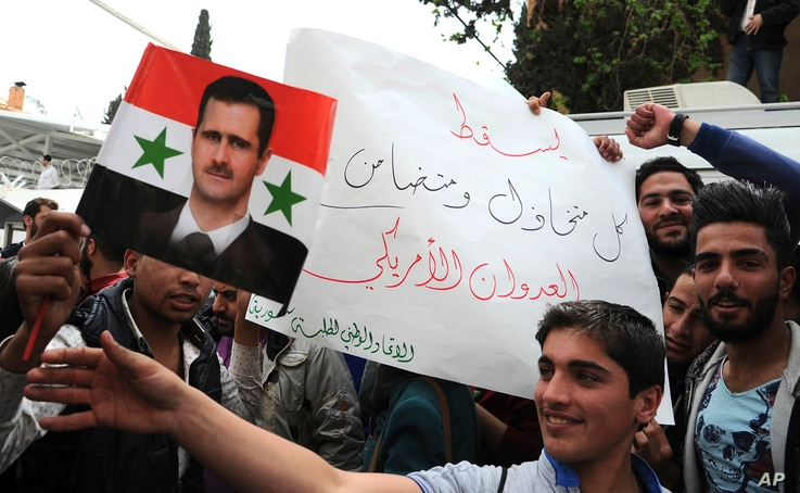 """In this photo released by the Syrian official news agency SANA, pro-government protesters hold a portrait of President Bashar Assad and a placard that reads, """"Down with everyone who cooperated and supported the American aggression,"""" during a protest ..."""