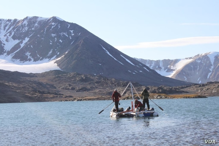 From this small platform perched atop two inflatable rafts, these scientists are able to take sediment cores from the lake floor below. (Credit: Marthe Gjerde)
