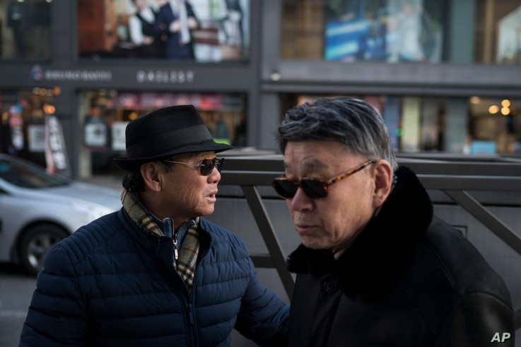 Song Hong, left, walks with his childhood friend Choi Kyu-Sik in downtown Gangneung, South Korea, Feb. 12, 2018.
