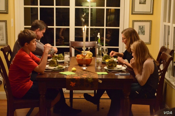Jane Rassmussen's family sits down to a dinner inspired by her recent cooking lessons. (VOA/S. Koster)