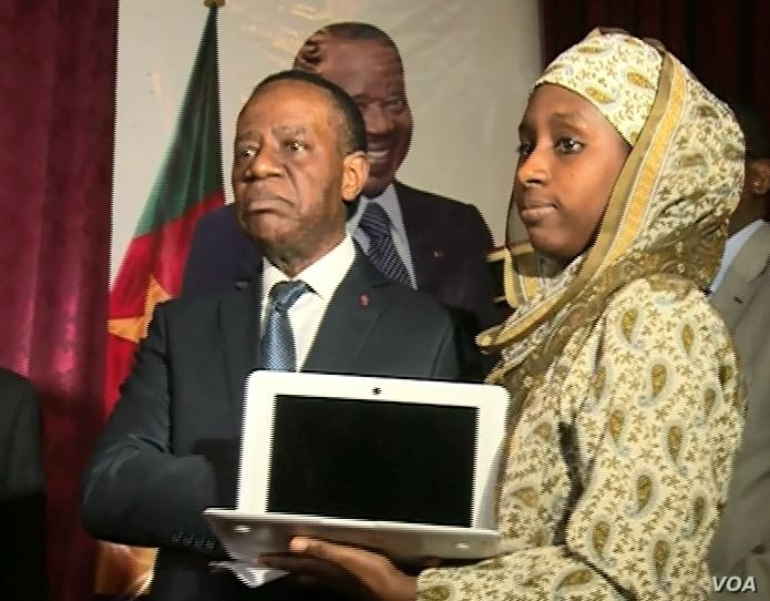 Cameroon's higher education minister, Jacques Fame Ndongo, hands a laptop to a female student, in Yaounde, Cameroon, Dec. 27, 2017. (M. Kindzeka/VOA)