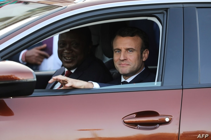 French President Emmanuel Macron, right, and Kenyan President Uhuru Kenyatta  take a test drive during the presentation of the new Peugeot 3008 Allure SUV at the State House in Nairobi, March 13, 2019.