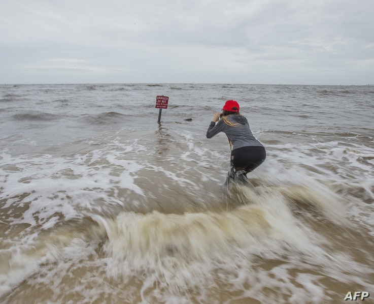 Hannah Jacole Powell-Yost takes photos of a danger sign in the Gulf surf in Gulfport, Miss., as Hurricane Nate approached the Mississippi Gulf Coast, Oct. 7, 2017.