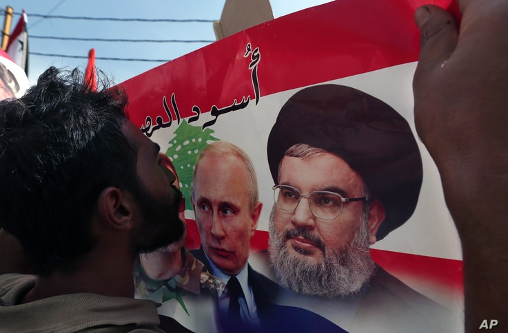 A Syrian who lives in Lebanon kisses a poster with photos of Russian President Vladimir Putin (C) and Hezbollah leader Sheikh Hassan Nasrallah, during a rally to thank Moscow for its intervention in Syria, in front of the Russian embassy in Beirut, L...