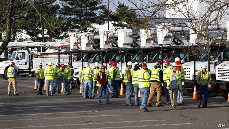 Crews from as far away as Missouri and Illinois gather in a parking lot used as a staging area at the Quaker Bridge Mall in Lawrence Township, N.J., November 1, 2012.