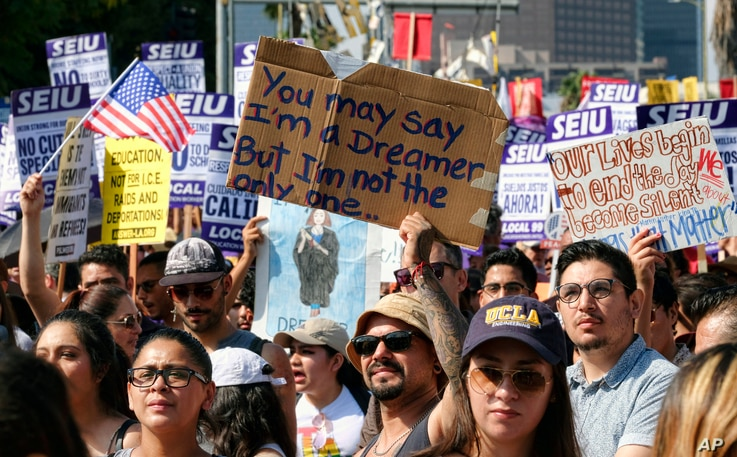 Supporters of the Deferred Action for Childhood Arrivals, or DACA chant slogans and hold signs while joining a Labor Day rally in downtown Los Angeles on Sept. 4, 2017.
