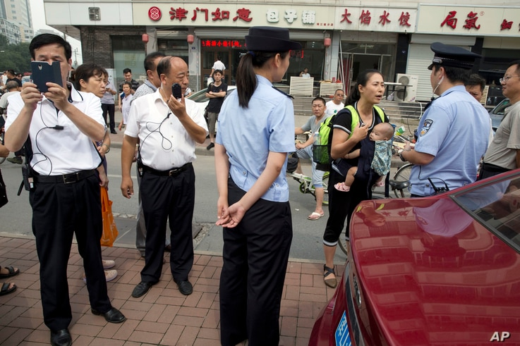 Yuan Shanshan, third right, the wife of detained Chinese lawyer Xie Yanyi, carries her child as she talks to a police officer while other plain clothes security personnel film journalists near the Tianjin No. 2 Intermediate People's Court in northern...