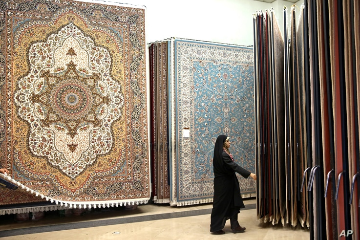 FILE - An Iranian female customer looks at the carpets in a shop in Tehran's old main bazaar, March 18, 2014. Iran's famed carpet weavers are busy following the country's historic nuclear deal with world powers in July, anticipating a boost in expo...