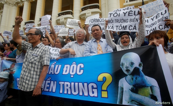 Demonstrators, holding signs to protest against Taiwanese enterprise Formosa Plastic and environmental-friendly messages, say they are demanding cleaner waters in the central regions after mass fish deaths in recent weeks, in Hanoi, Vietnam, May 1, 2...