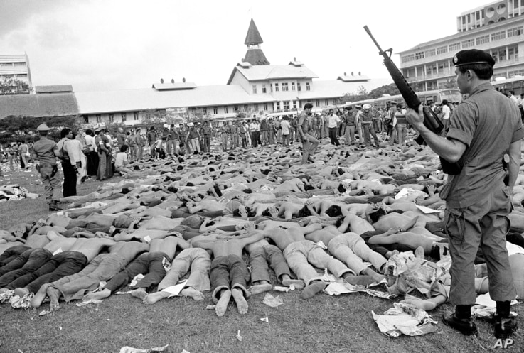 FILE - In this Oct. 6, 1976 file photo, police stand guard over leftist Thai students on a soccer field at Thammasat University, in Bangkok, Thailand. For some Thais, the bloody events of October 6, 1976 are still a nightmare. On that day, heavily ar...