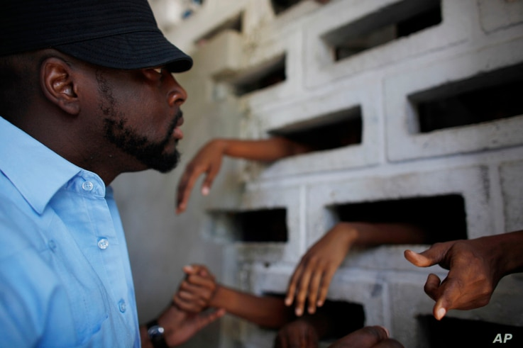 Haitian musician Wyclef Jean speaks to inmates at the women's annex of the National Prison in Port-au-Prince, June 16, 2010. Jean says he is in Haiti to distribute aid to people displaced by the January earthquake and to fight for better prison condi...