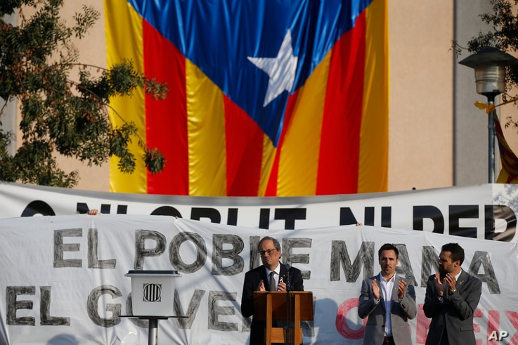 Catalan regional President Quim Torra (C) applauds in front of a large Catalonia independence flag during a rally in Sant Julia de Ramis, Spain, Oct. 1, 2018.