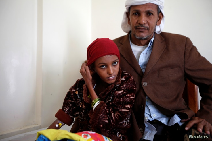 Saida Ahmad Baghili, 18, who has been affected by severe malnutrition, sits with her father at a hotel in Sanaa, Yemen, Dec. 4, 2016.