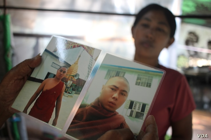 Daw Aye holds a photo of her son, who died after being taken into police custody last year (J. Carroll/VOA)