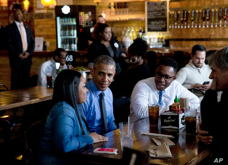 President Barack Obama has lunch at the Jolly Pumpkin Brewery in Detroit, Wednesday, Jan. 20, 2016, with from left, Teana Dowdell, autoworker at the General Motors' Detroit-Hamtramck Assembly, Dr. Tolulope Sonuyi, Emergency medicine physician engag...
