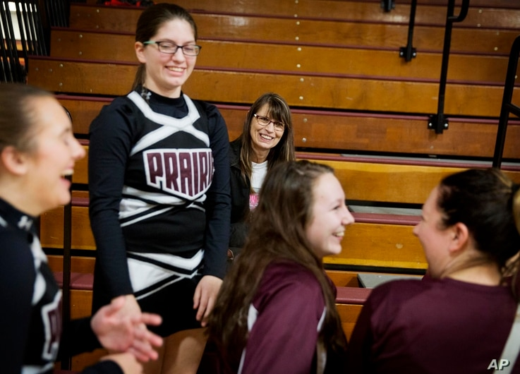 Marlene Kramer, center, attends a wrestling meet to watch her stepdaughter Sierra, 16, center left, cheerlead at a high school wrestling meet in Prairie du Chien, Wis., Jan. 19, 2017.