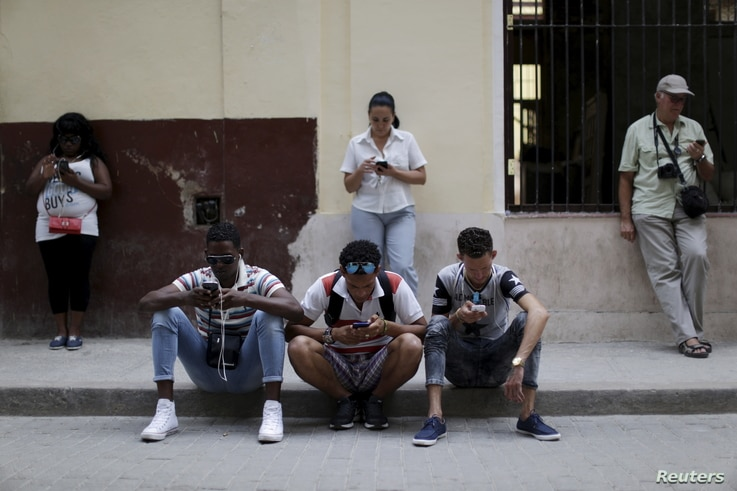 People sit and stand near a Wi-Fi hotspot in Havana, March 17, 2016.