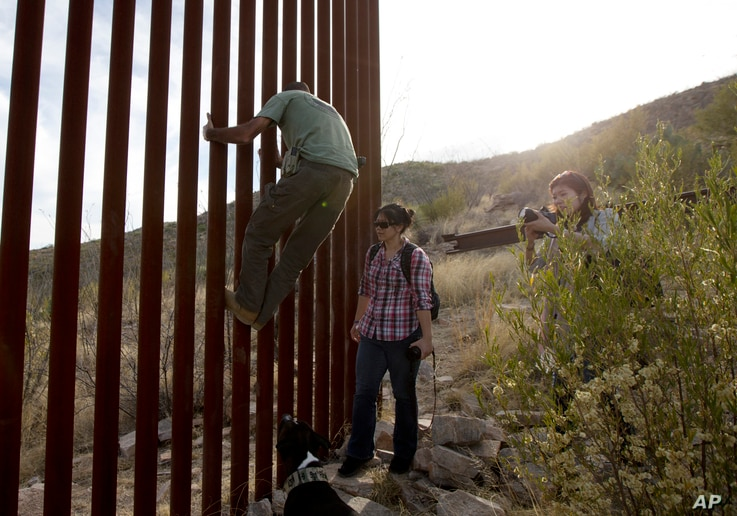 FILE - In this May 11, 2016, photo, former construction foreman Tim Foley shows how to climb a section of the border wall separating Mexico and the United States near where it ends as journalists Chitose Nakagawa, right, and Marcie Mieko Kagawa look ...