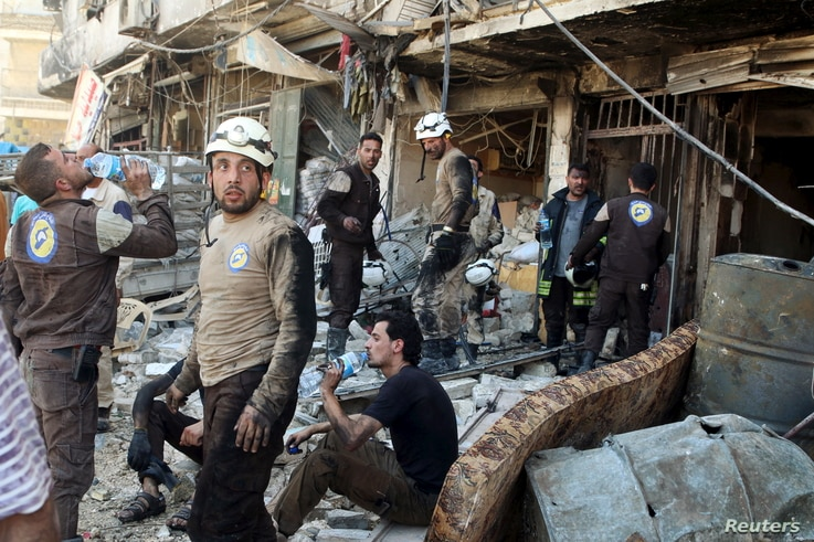 Civil defense members rest amid rubble of damaged buildings after an airstrike on the rebel-held Tariq al-Bab neighborhood of Aleppo, Syria, April 23, 2016.