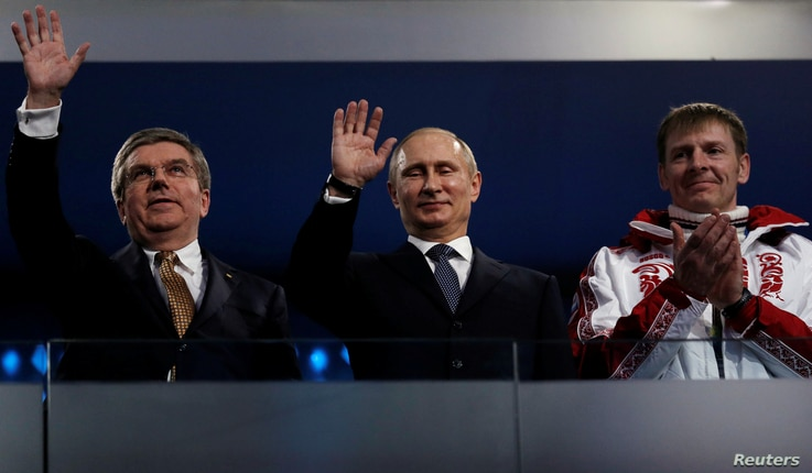 FILE - International Olympic Committee (IOC) President Thomas Bach of Germany and Russian President Vladimir Putin wave as gold medalist bobsleigh athlete Russia's Alexander Zubkov applauds during the closing ceremony for the 2014 Sochi Winter Olympi...