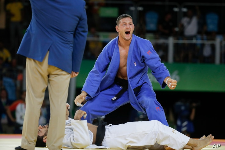 Czech Republic's Lukas Krpalek, blue, reacts after winning the gold medal against Azerbaijan's Elmar Gasimov during the men's 100-kg judo competition at at the 2016 Summer Olympics in Rio de Janeiro, Brazil, Aug. 11, 2016.