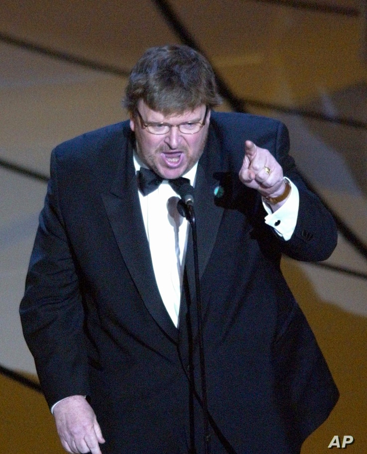 """FILE - Michael Moore makes a statement after accepting the Oscar for best documentary feature for the film """"Bowling for Columbine"""" during the 75th annual Academy Awards, March 23, 2003, in Los Angeles."""