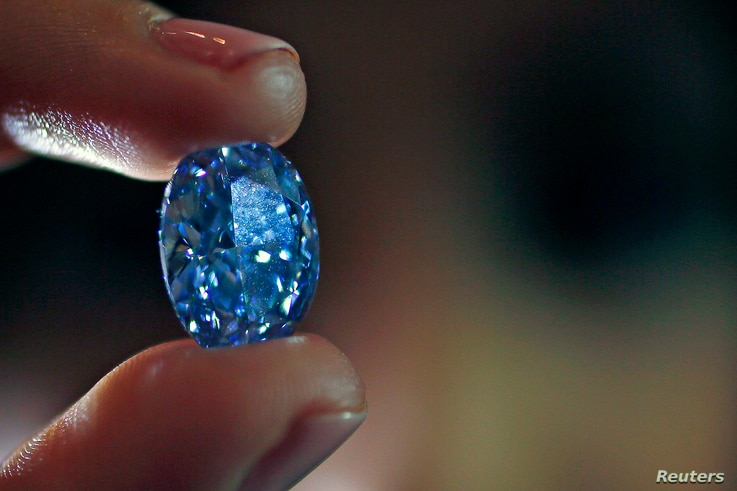 An employee holds a 10.10-carat internally flawless blue diamond at Sotheby's auction house in London, March 15, 2016.