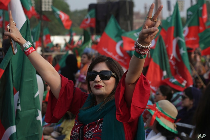 FILE - A supporter of opposition leader Imran Khan's party Tehreek-e-Insaf flashes victory signs during a rally in Lahore, Pakistan, April 29, 2018.