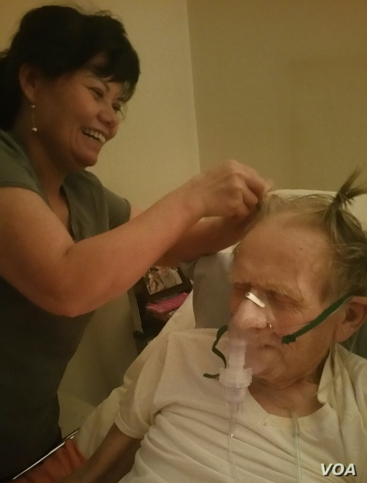 Nguyễn Thị Kim Nga, left, plays with Gary Wittig's hair while taking care of him in Riverdale, Georgia.
