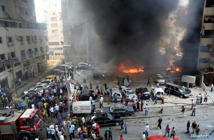 Civil Defense members, security personnel and civilians gather at the site of an explosion in Beirut's southern suburbs, July 9, 2013.
