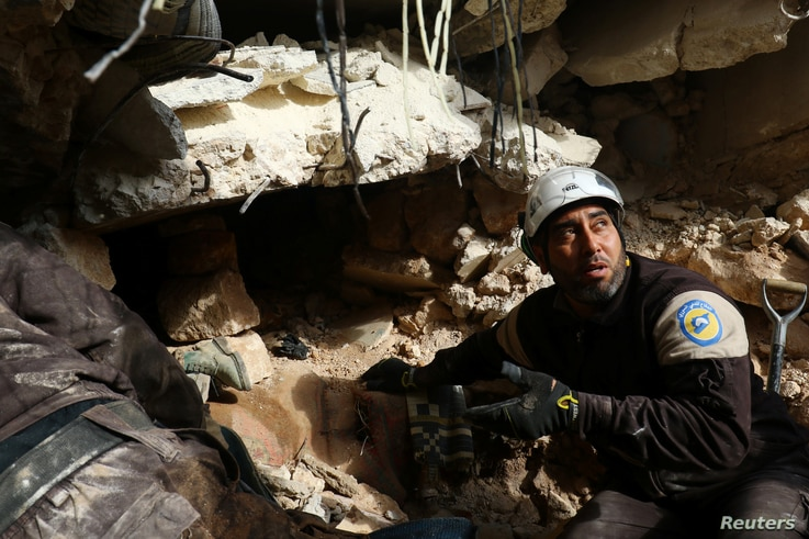 Civil Defense members look for survivors under rubble of damaged buildings after airstrikes on the northern neighborhood of Idlib city, Syria, Dec. 5, 2016.