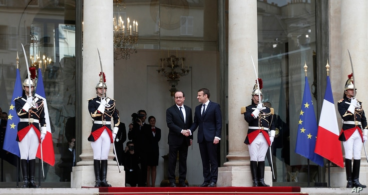 Outgoing French President Francois Hollande, center left, welcomes incoming French President Emmanuel Macron as he arrives for his inauguration ceremony at the Elysee palace in Paris,  May 14, 2017.