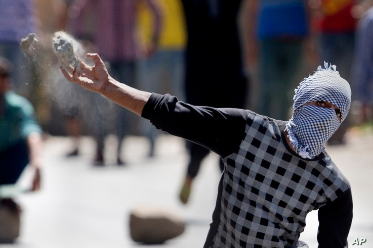 A masked Kashmiri protester throws a rock at policemen in Srinagar, India, Friday, July 8, 2016. Youths in the Indian portion of Kashmir clashed with police during a protest against allegations that Islamic preacher Zakir Naik was involved in making ...