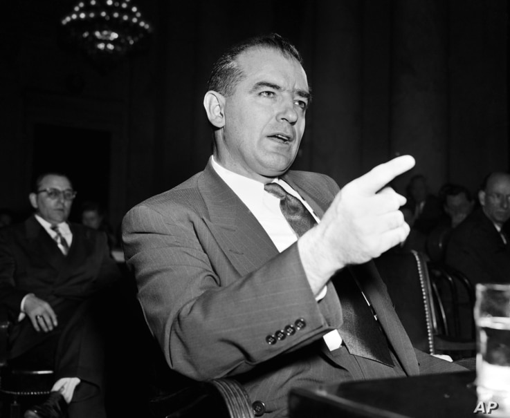 FILE - Sen. Joseph McCarthy gestures during a Senate subcommittee hearing in Washington on McCarthy's charges of communist infiltration of the U.S. State Department, March 9, 1950.