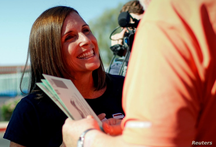 Republican candidate Martha McSally talks to Dennis Williams of Mesa, Arizona as he heads to the polls to vote in the Republican primary for the open U.S. Senate seat, in Mesa, Arizona, Aug. 28, 2018.