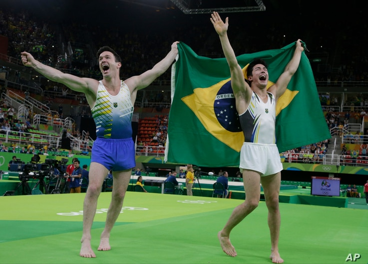 Brazil's Arthur Mariano, right, and compatriot Diego Hypolito celebrate with their national flag after winning bronze and silver respectively for the floor during the artistic gymnastics men's apparatus final at the 2016 Summer Olympics in Rio de Jan...