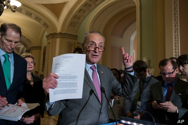 FILE - Senate Minority Leader Chuck Schumer of New York, joined by, from left, Sen. Ron Wyden, D-Ore., the ranking member of the Senate Finance Committee, and Sen. Debbie Stabenow, D-Mich., holds up a letter he sent to President Donald Trump, Senate ...