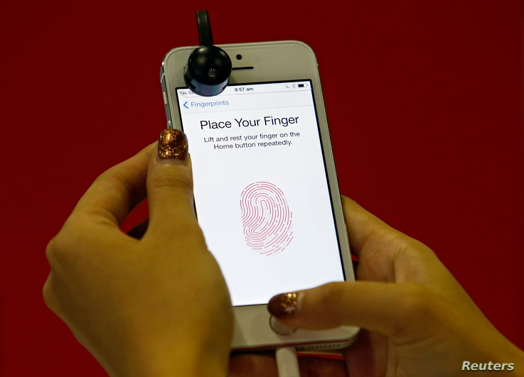 A promoter demonstrates the fingerprint scanner feature of the newly launched Apple iPhone 5S in Singapore, Sept. 20, 2013.