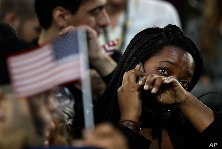 FILE - a woman weeps as election results are reported during Democratic presidential nominee Hillary Clinton's election night rally in the Jacob Javits Center glass enclosed lobby in New York.
