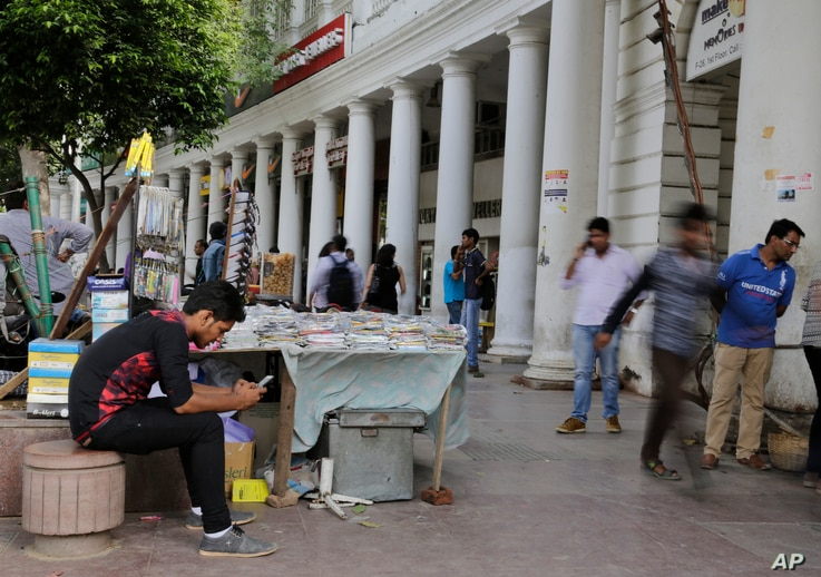 FILE - An Indian man, left, uses his mobile phone as people walk past in New Delhi, India.