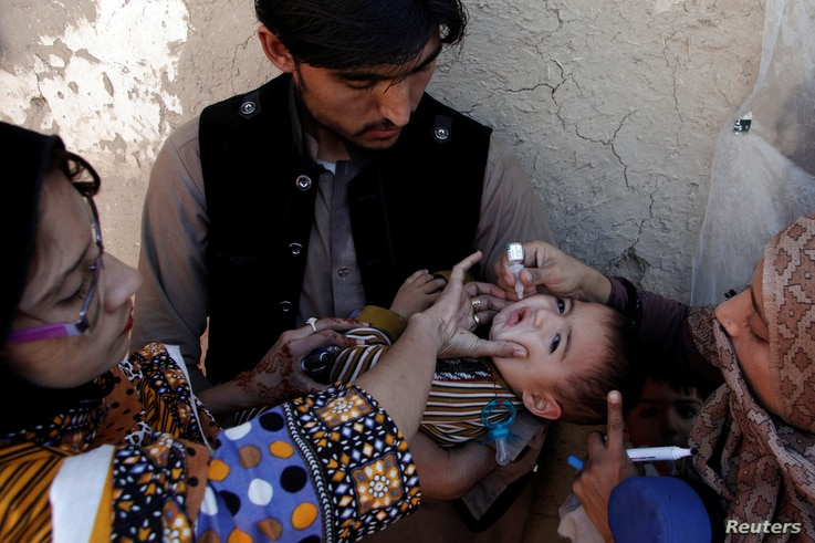 Vaccination workers give a boy polio vaccine drops on a street in Quetta, Pakistan, Jan. 2, 2017.
