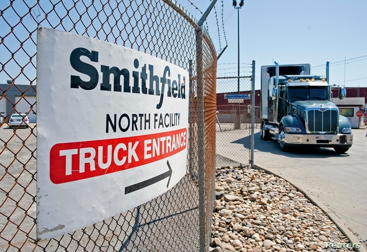 Trucks make their way around the Smithfield Foods packaging plant in Smithfield, Virginia, May 30, 2013.